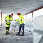 Karriere: To personer står over plantegninger på byggeplass.